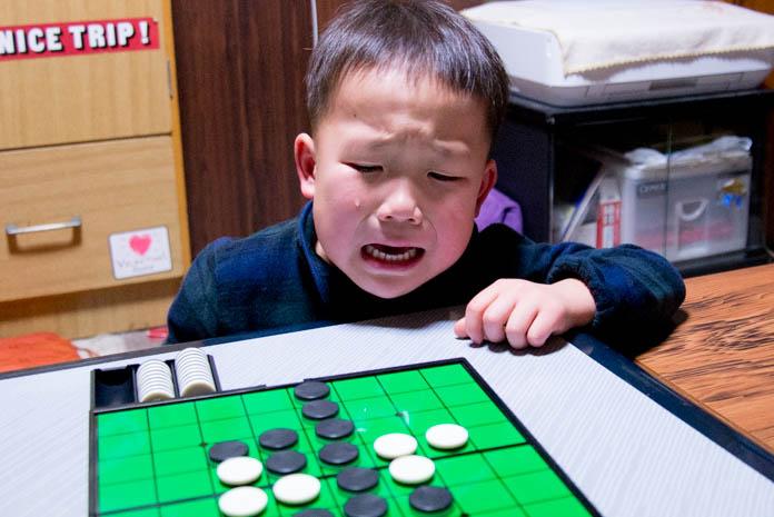 オセロの盤を前に悔し泣きする息子(4歳の男の子)