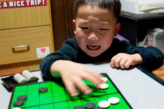 オセロの盤をぐちゃぐちゃにする息子(4歳の男の子)