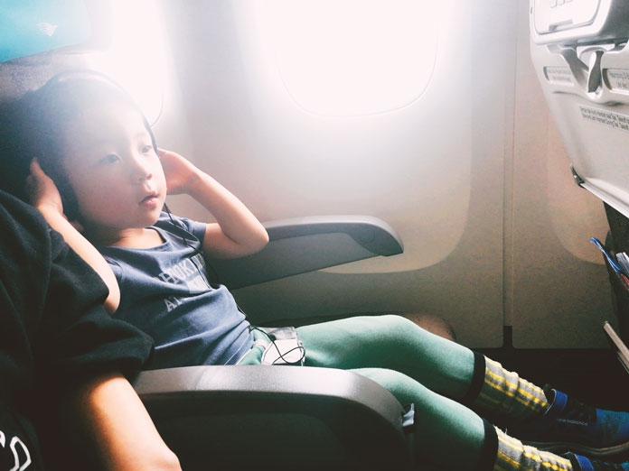 飛行機の座席でくつろぐ男の子