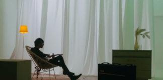 揺れるカーテンの前でギターを弾く須田景凪さん