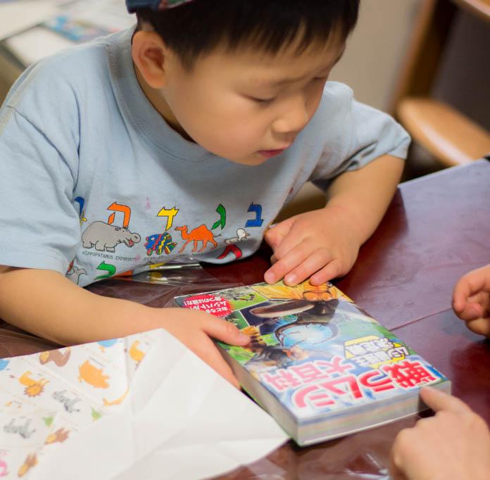 誕生日プレゼントに「戦うムシ大百科 ムシ最強王決定戦」をもらって表紙を眺める息子