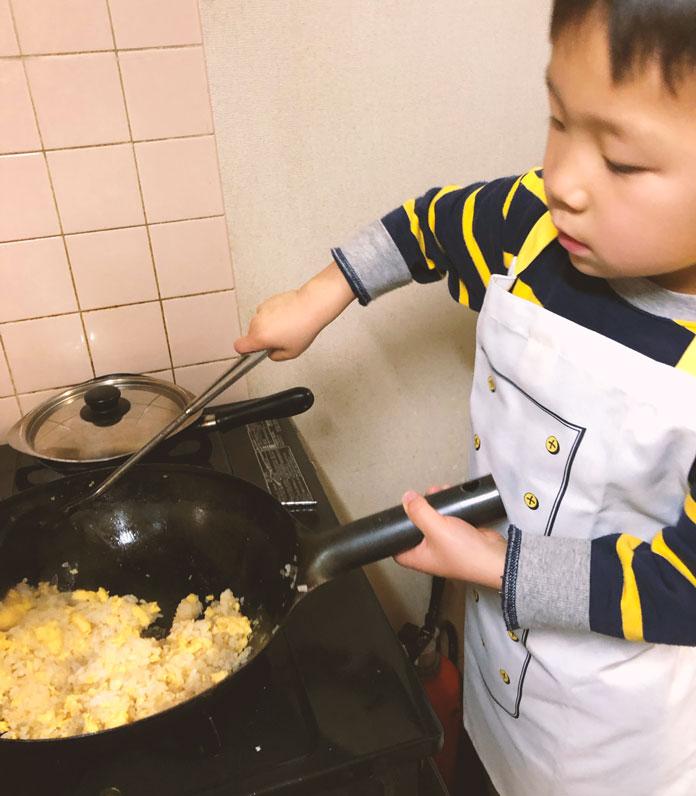 中華鍋を振ってチャーハンを作る4歳の息子