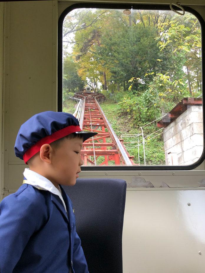 展望露天風呂「雲の助」へつなぐ登山電車(トロッコ)から外を眺める子ども