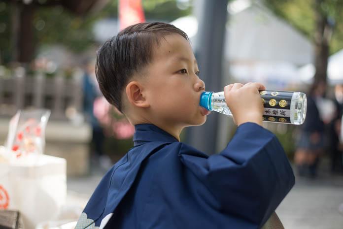羽織袴でラムネを飲む5歳の男の子