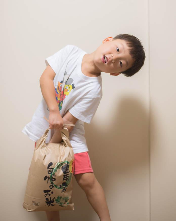 5kgの米袋を持つ5歳の男の子