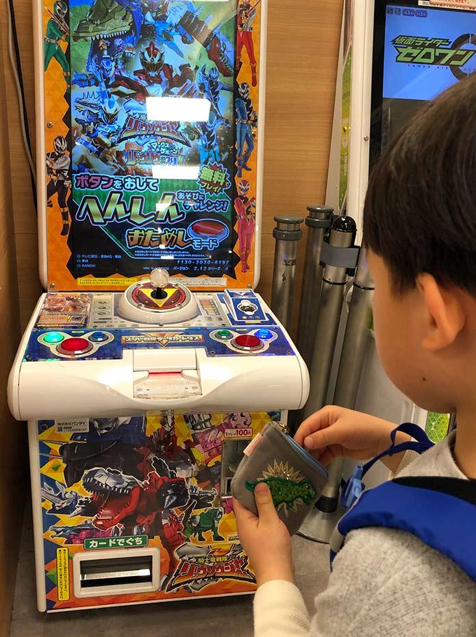 おもちゃ売り場にある、スーパー戦隊のゲームをやろうとしている子ども