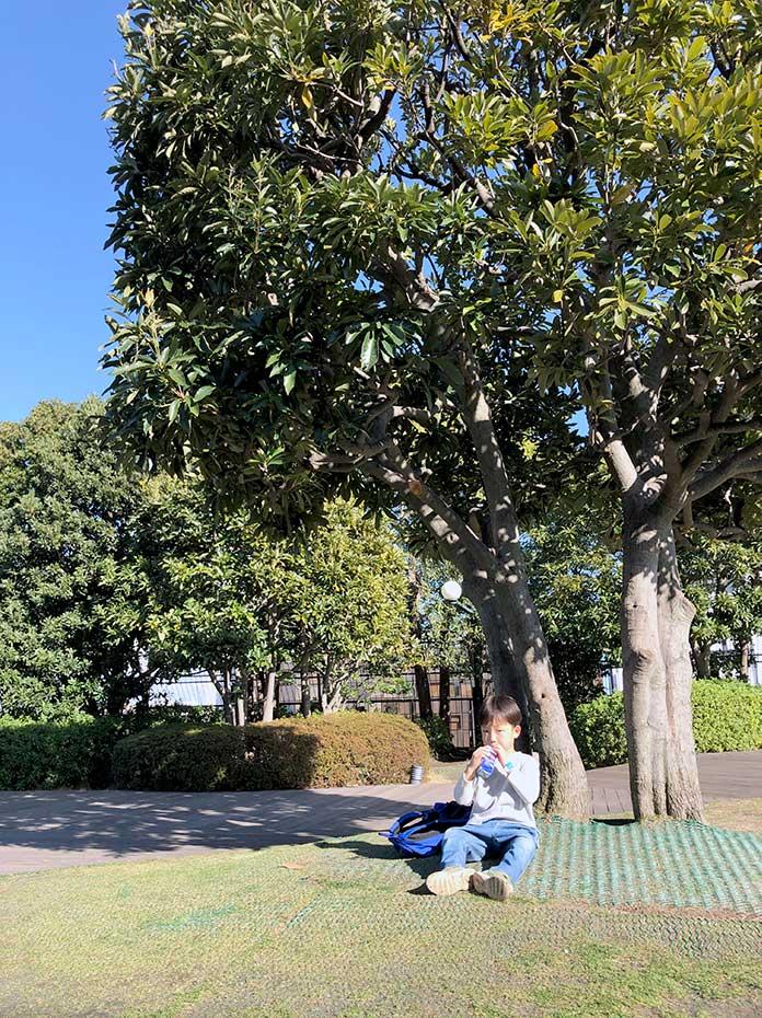 玉川高島屋の屋上、木陰でジュースを飲む子ども