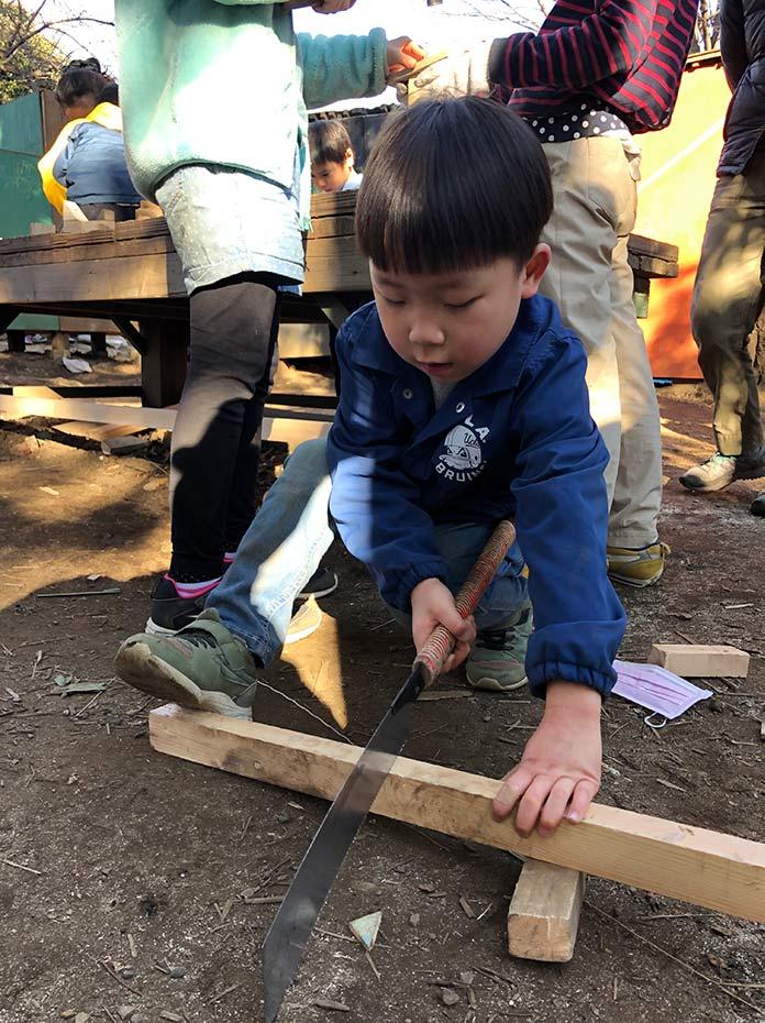 ノコギリで木を切る子ども 羽根木公園プレーパーク