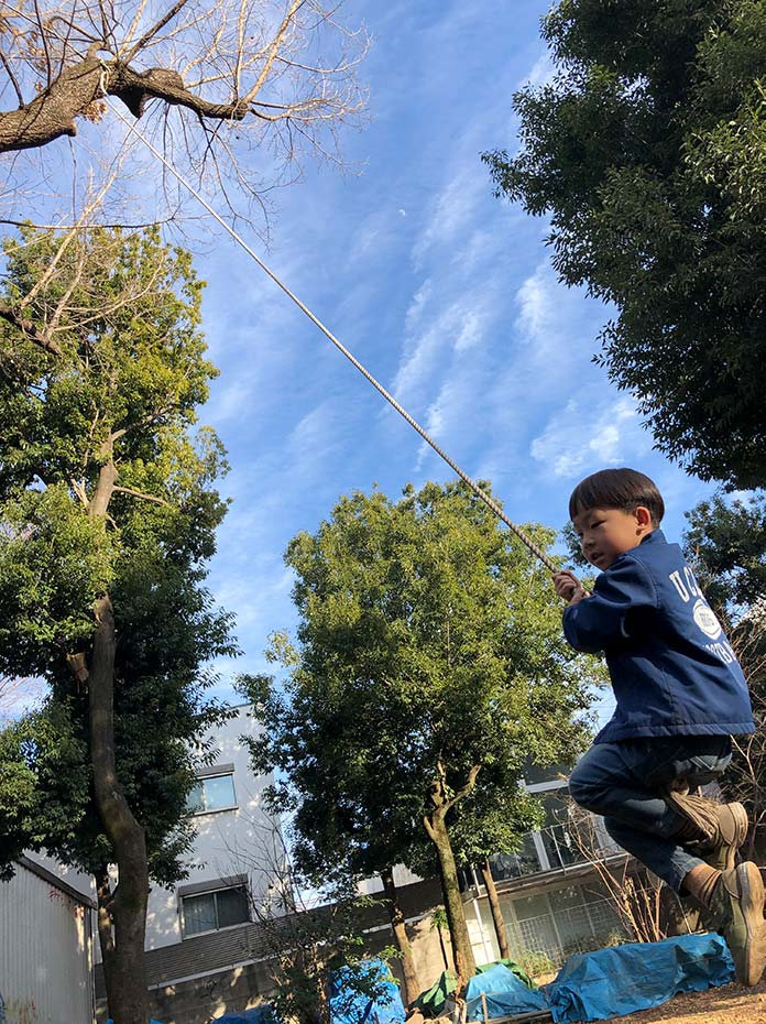 木にぶら下げたターザンロープで遊ぶ子ども 羽根木公園プレーパーク