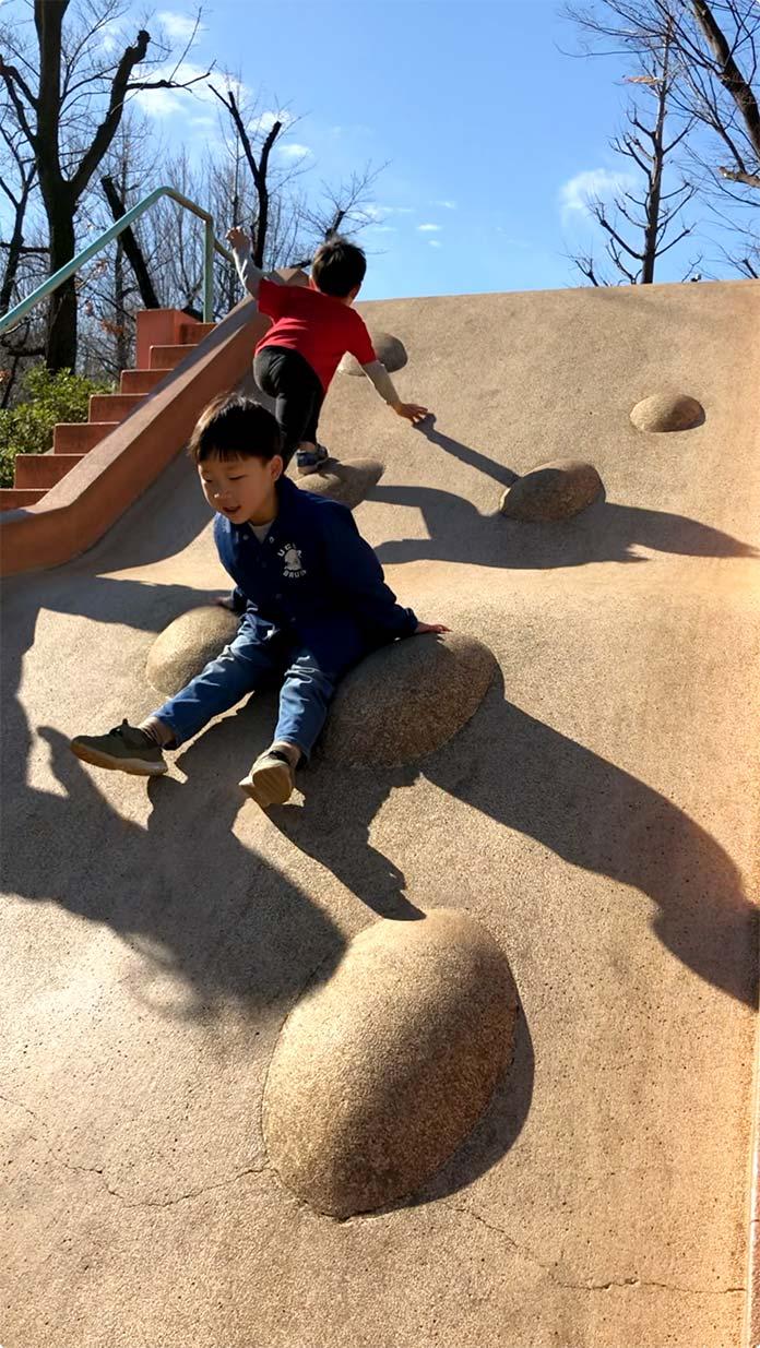 すべり台を滑る子ども 羽根木公園