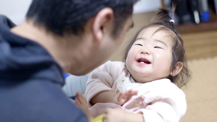 赤ちゃんをあやして笑わせるパパ