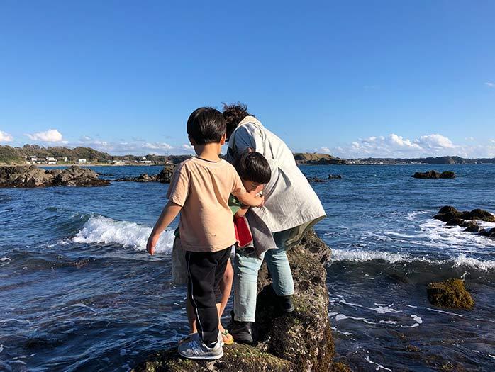 三浦半島の海岸の岩の上を歩く子どもたち