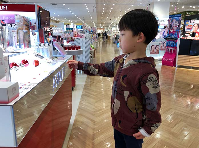 化粧品売り場を歩く5歳の息子
