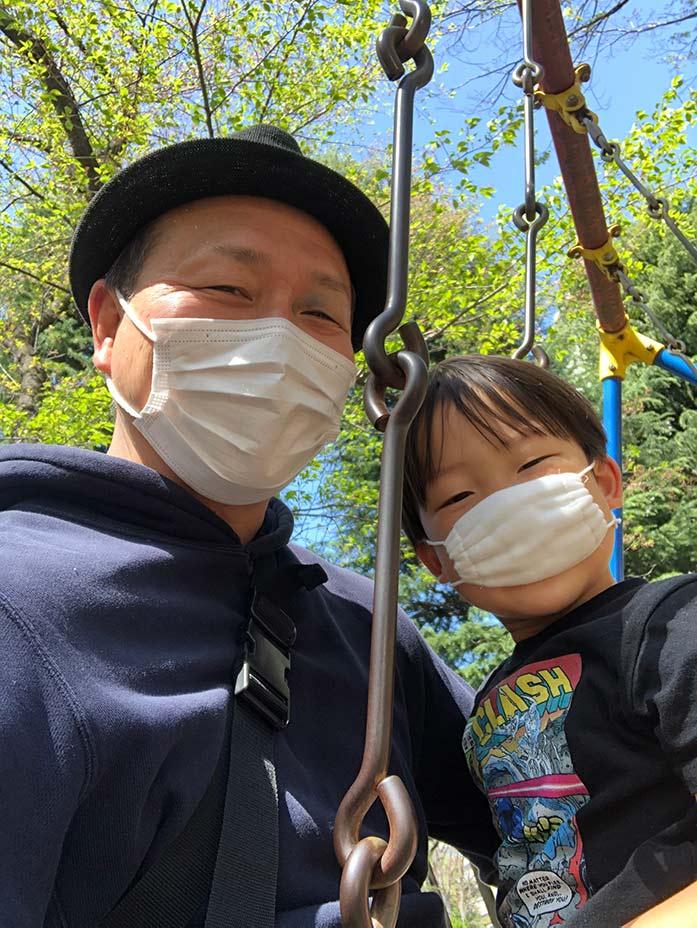 マスクをつけて公園で遊ぶパパと5歳の息子