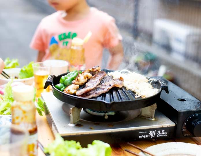 ガスコンロとジンギスカン鍋を使って肉を焼いているところ