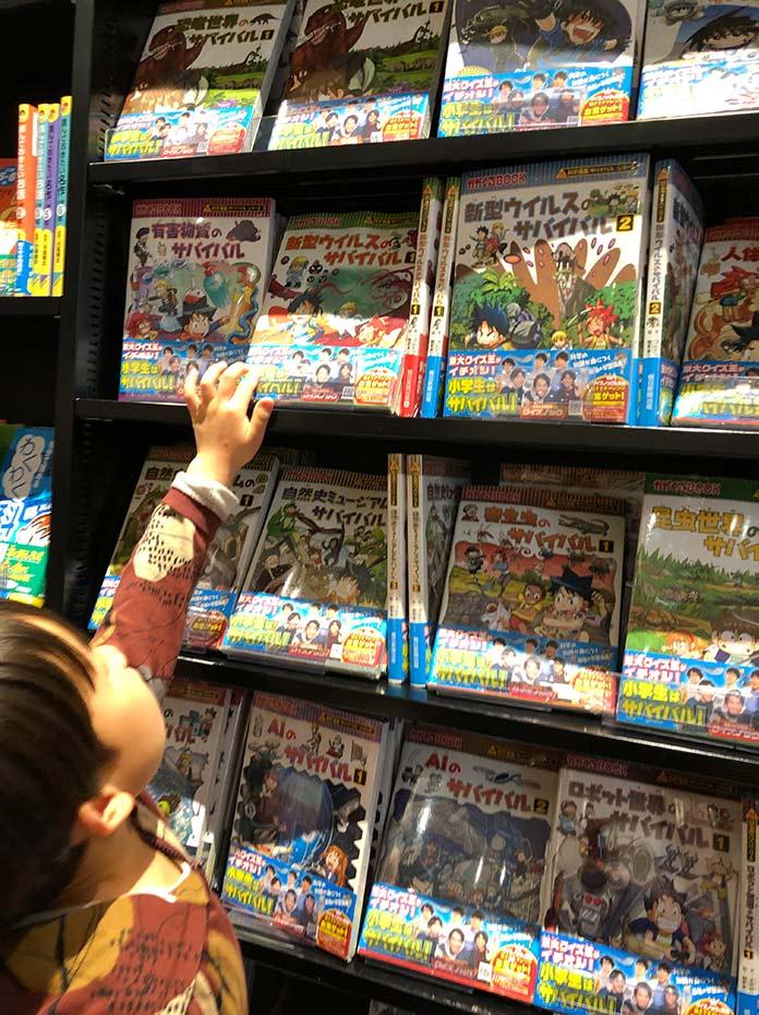 書店に並ぶ「かがくるBOOK サバイバルシリーズ」を手にとる子ども
