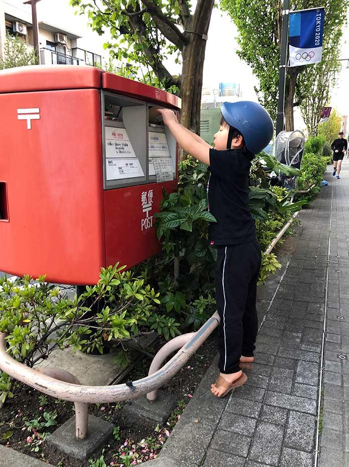 ポストに封筒を投函する5歳児