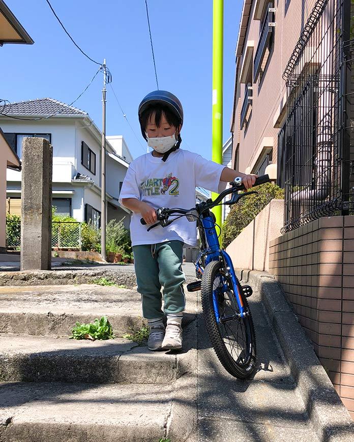 公道で自転車の練習をする息子