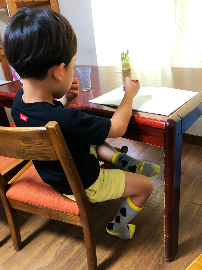 ダイニングテーブルでノートを広げている6歳の息子