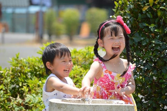 笑顔で水遊びする子ども(兄弟)