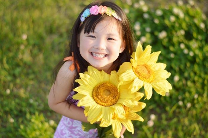 大きなひまわりを抱えた笑顔の女の子