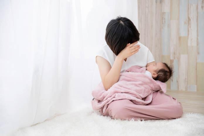 赤ちゃんを抱き抱えて泣いている母親