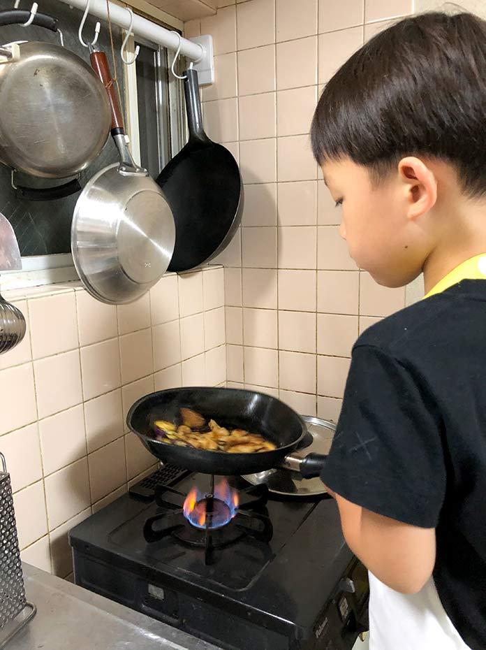 フライパンで炒め物をする子ども