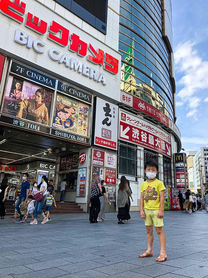 渋谷TOEI 前でマスクをつけて立つ子ども