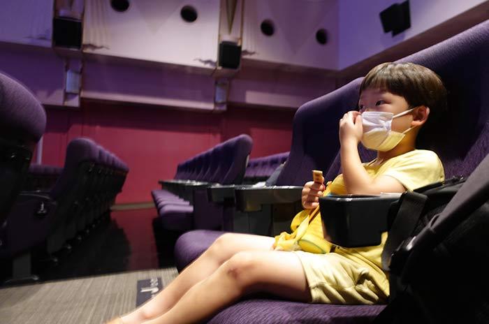 マスクをつけて映画館のシートに座る6歳の息子