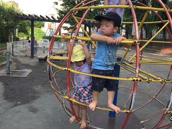 回るジャングルジム「グローブジャングル」で遊ぶ3歳児