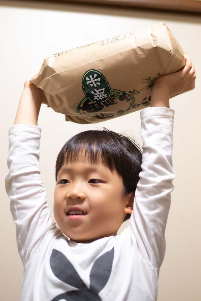 米袋を担ぎ上げる子ども 6歳