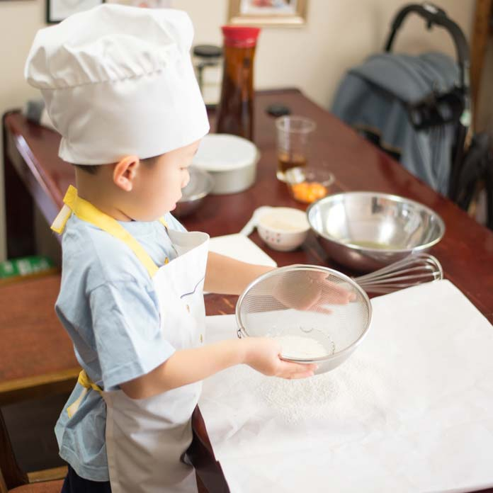 ケーキづくりをしている6歳児