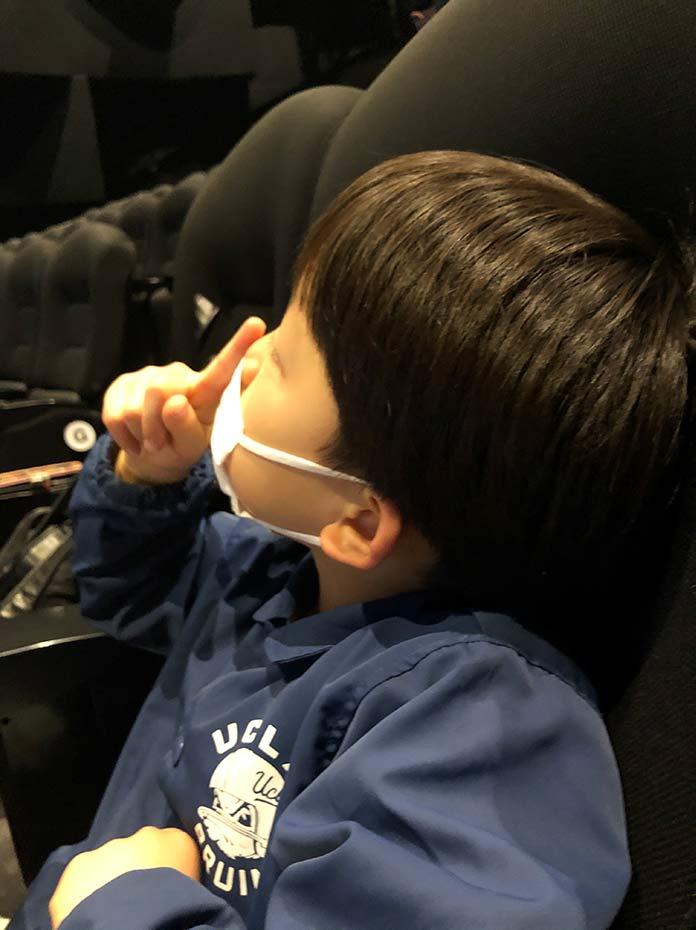 映画館のシートに座る6歳の息子