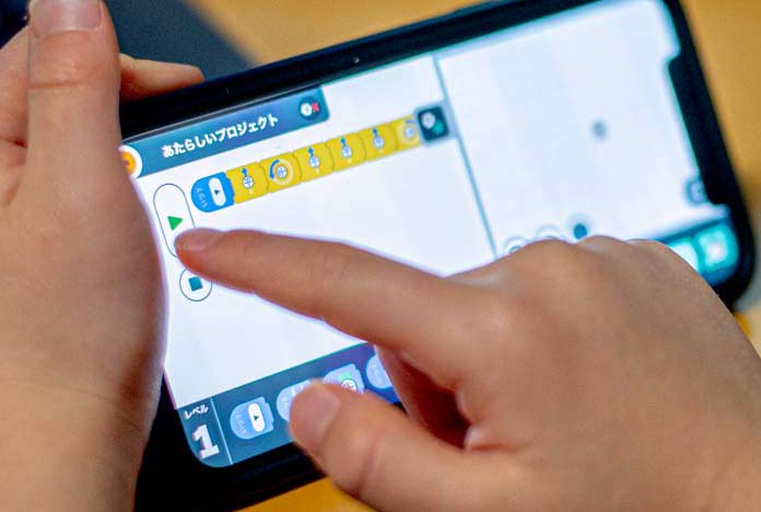 iPhoneアプリ「iRobot Coding」を使っている子ども