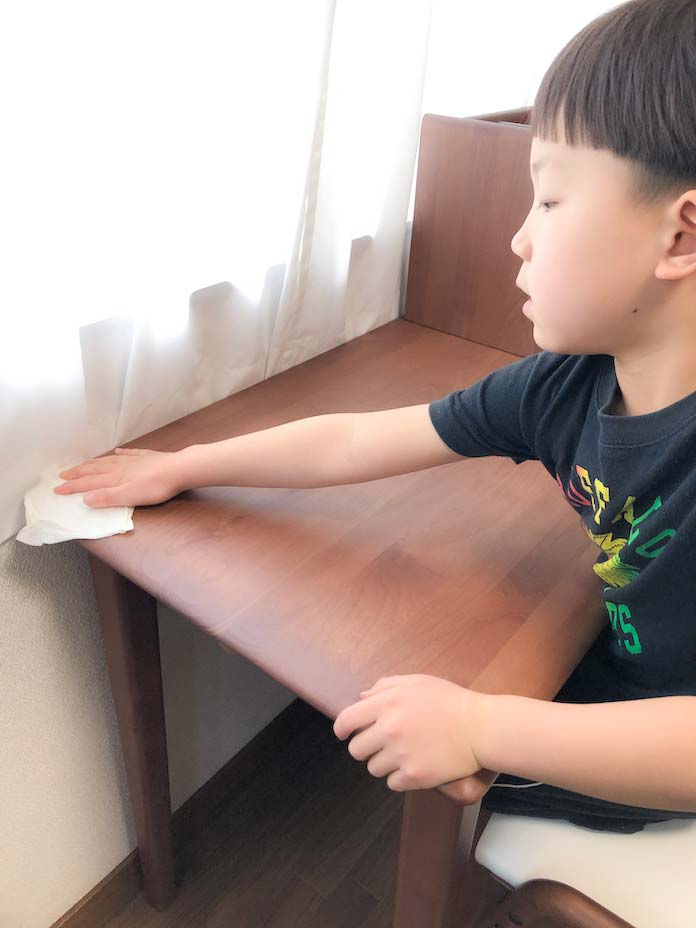 学習デスクの天板を拭く息子