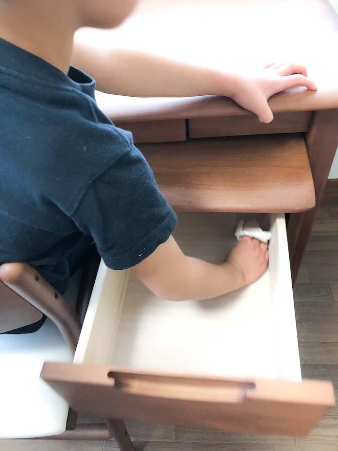 袖机の引き出しの中をを拭く息子