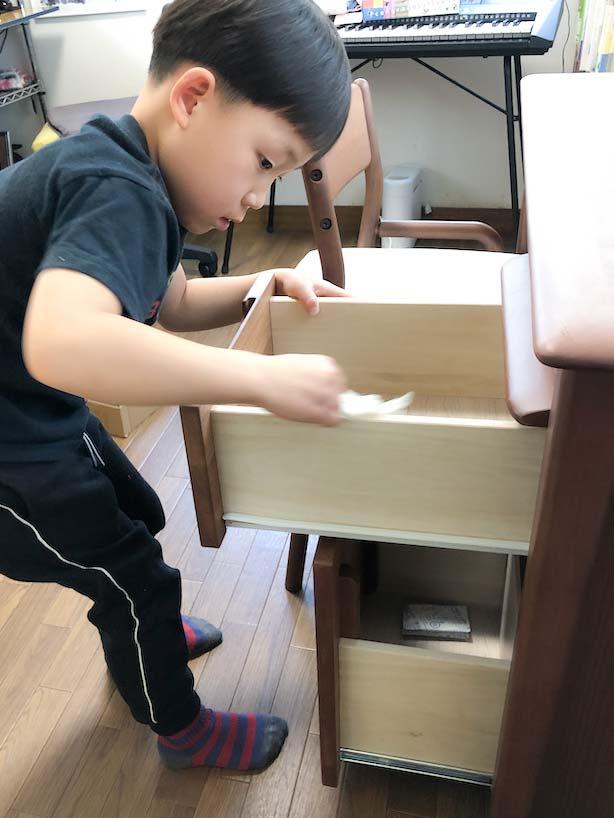 袖机の引き出しのふちをを拭く息子