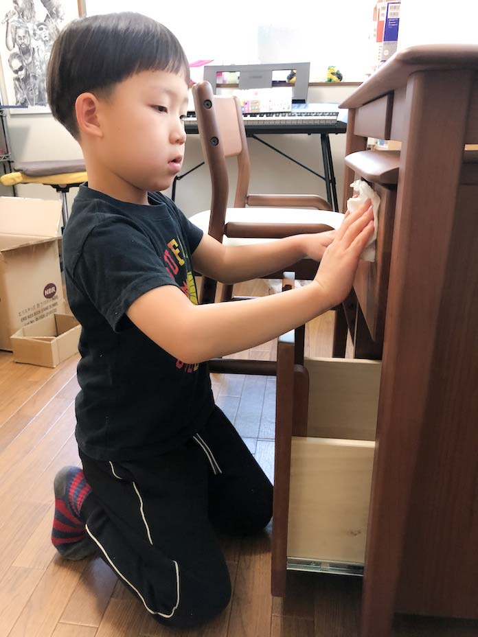 学習机の周りを拭く息子