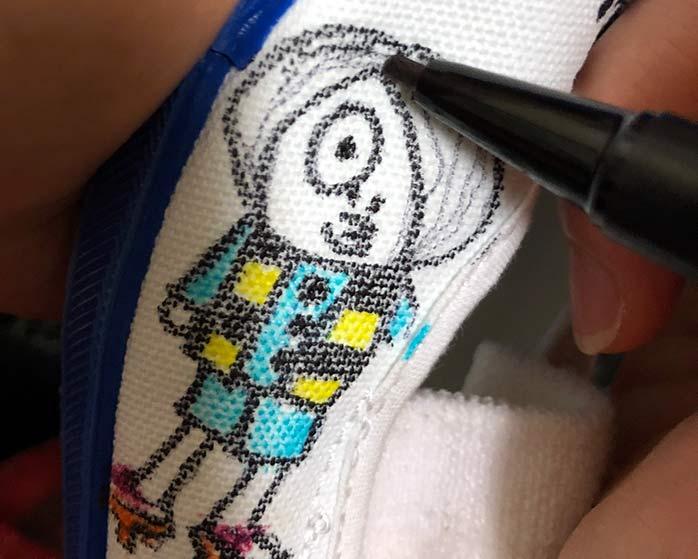 ぬのぺんで子どもの上履きに絵を描いているところ