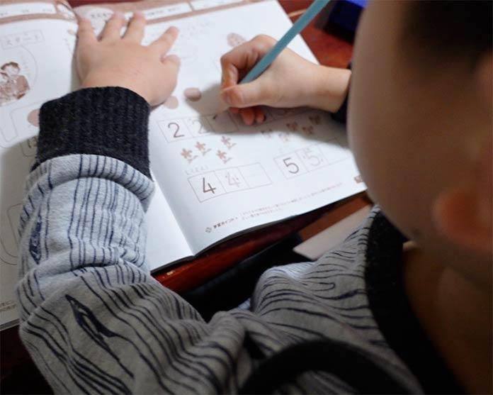 数字の書き方を練習する年長の息子