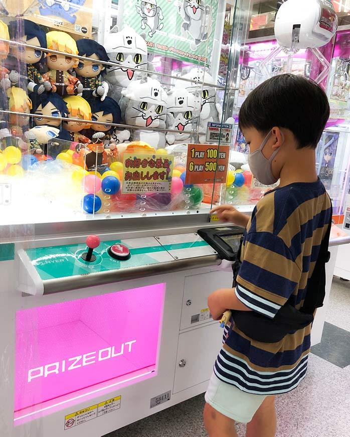 クレーンゲームにチャレンジする子ども(7歳)