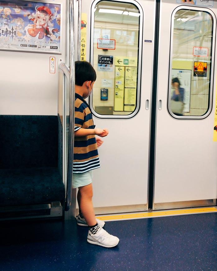 電車に乗って立っている子ども