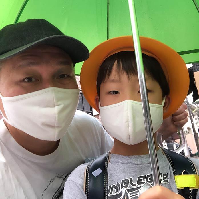 マスクをつけて登校する小学1年生の子供と親