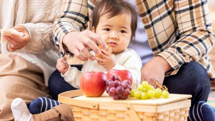 赤ちゃんがパンやフルーツを食べている