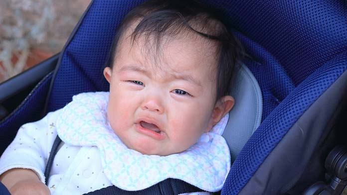 ベビーカーに乗って泣いている赤ちゃん